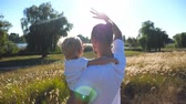 scène rurale : Father and little child waving their hands at the meadow. Young dad holding his son on arms at nature. Happy family spending time together. Summer landscape at background. Close up Rear back view