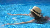 Young beautiful girl in sunglasses and hat swimming in pool. Woman relaxing in clear warm water on sunny day. Summer vacation or holiday concept. Close up Slow motion Stock Footage