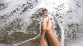 неузнаваемый : Sea waves washing over tanned female feet. Beautiful girl lying on the beach on a sunny day. Young woman relaxing at coast during summer vacation or holiday. Top view Slow motion Close up