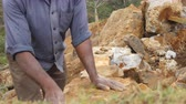 hitting : Side view of unrecognizable indian man cutting a block of granite with hammer in park. Adult human hitting stone with sledgehammer for construction flowerbed. Stonemason carving. Close up Stock Footage