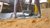 Low angle view of unrecognizable indian men shoveling manually wet cement in pile at building site. Local builders working on construction area. Concept of future project. Close up Stock Footage