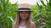 olhares : Close up of little smiling girl in straw hat looking into camera in meadow at organic farm. Portrait of happy small child with long blonde hair standing against the blurred background of corn field