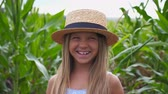 olhares : Portrait of beautiful funny girl in straw hat looking into camera and laughs covering her face with hand. Happy little kid standing with joyful smile against the blurred background of corn field