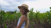 olhares : Attractive little girl in straw hat standing at corn field turning to camera and smiling. Small kid with long blonde hair looking at maize plantation and enjoying nature landscape. Close up Slow mo Stock Footage