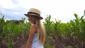 olhares : Close up of beautiful little girl in straw hat standing at corn field, turning to camera and smiling. Small kid with long blonde hair looking at maize plantation and enjoying nature landscape. Slow mo