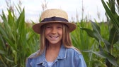 olhares : Beautiful little girl in straw hat looking into camera and laughing in the meadow. Portrait of happy small child with long blonde hair standing against the blurred background of corn field. Close up Stock Footage