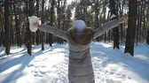 неузнаваемый : Back view of young woman walking in sunny winter forest. Unrecognizable girl enjoying stroll through snowy wood raising her hands. Carefree lady having fun outdoor. Beautiful landscape. Slow motion