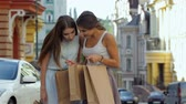 shoppingbag : Photo of attractive girls expressing joy of her new purchase, happy good looking girl with shopping bags walking , money spending and  antistress concept, autumnal sale Stock Footage