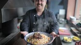 braised dishes : The chef shows on camera plate of pilaf with lamb.