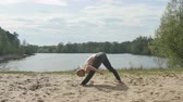 wellbeing : The yogi training outside on the sand near the river Stock Footage