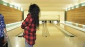 bowling alley : Man play bowling, his friends observes after him