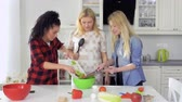 vegeterian : Young girls cooks salad and mix fresh cutting vegetables in a bowl