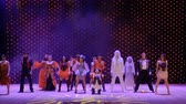 необычный : Different heroes in scenic costumes are dancing in theatre
