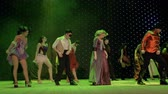 role : Group of fairytale heroes are dancing and singing on stage in theatre