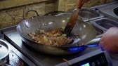rice pan : Chef mixes rice noodles and fried vegetables with spatula in a hot pan Stock Footage