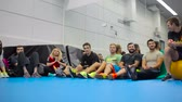esportivo : The team of young people sits on floor in the gym on the training