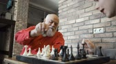 ладья : Senior man play chess with granddaughter at home
