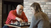 parentes : Young girl play chess with her grandpa