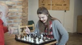 шах и мат : Young beautiful girl play chess with grandfather Стоковые видеозаписи