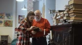 detetive : Gray-haired grandfather and granddaughter read interesting book together