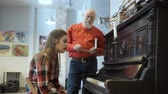 относительный : Young girl doesnt get to play well on the piano, the grandpa calms down her Стоковые видеозаписи