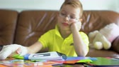 workbook : Little boy with broken hand dont want to make his school homework Stock Footage