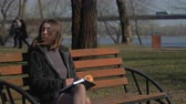 organizador : Pretty girl eats apple on the bench in park, and makes notes in notebook Vídeos