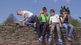 четыре человека : Four teens sits at concrete wall in park