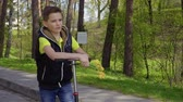 narcissus : Cute boy with bouquet of flowers riding on kick scooter in park Stock Footage