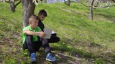 workbook : Two boys discusses school homework sitting under the tree in park