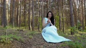 poisoned : Beautiful woman in long blue dress eat apple in the forest