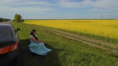 ábrándozás : Young woman sit on roadside near her car and enjoy beautiful canola flower field