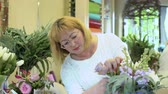 kwiaciarnia : Mature woman make flower composition Wideo