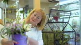 floristic : Mature woman with flower composition in flower shop Stock Footage