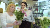 floristic : Florist and assistant create flower bouquet with roses and tulips