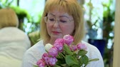floristic : Attractive mature woman with bouquet of roses and tulips Stock Footage