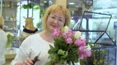 floristic : Smiling mature woman with bouquet of roses and tulips Stock Footage