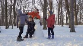 sněhulák : Playful kids high-fiving with each other near snowman in winter park