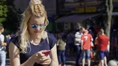 koncentrált : Young girl in sunglasses using phone