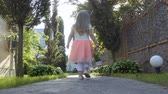 quintal : Beautiful little girl in lovely dress walk among trees in the garden