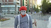 gesticulation : Mime in red beret has fun on camera at fountain background
