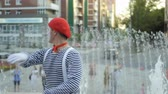 condutor : Funny mime conducting and has fun at the fountain background