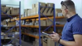 auditor : Inspector use tablet in warehouse at blurred background of shelves with products Stock Footage