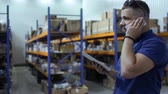 estoque : Inspector talking on phone standing at blurred background of warehouse Stock Footage