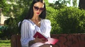 роман : Stylish woman in sunglasses read book in park