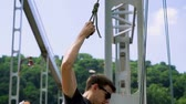 adrenaline : Young man fastens a rope to a carbine for jumping from the bridge