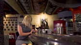 banquinho : Adult woman using phone sitting at bar counter in restaurant and drink wine Vídeos