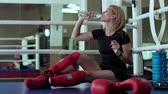 tükenme : Tired woman sit at the corner of boxing ring and drink water