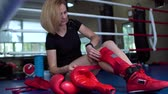 rękawice bokserskie : Woman put protection at her legs before fight at boxing ring Wideo