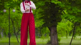 stilts : Funny mime walks on stilts and juggling in the park
